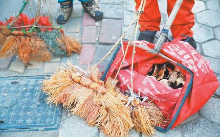 清扫完落叶,赵庆霞收拾工具,王钱男穿上棉袄,准备回家.图片