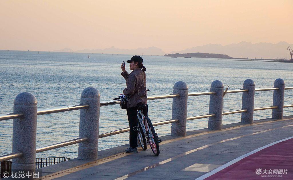 4月7日,青岛西海岸新区唐岛湾一湾碧水荡漾着春波,游人和市民在这迷人