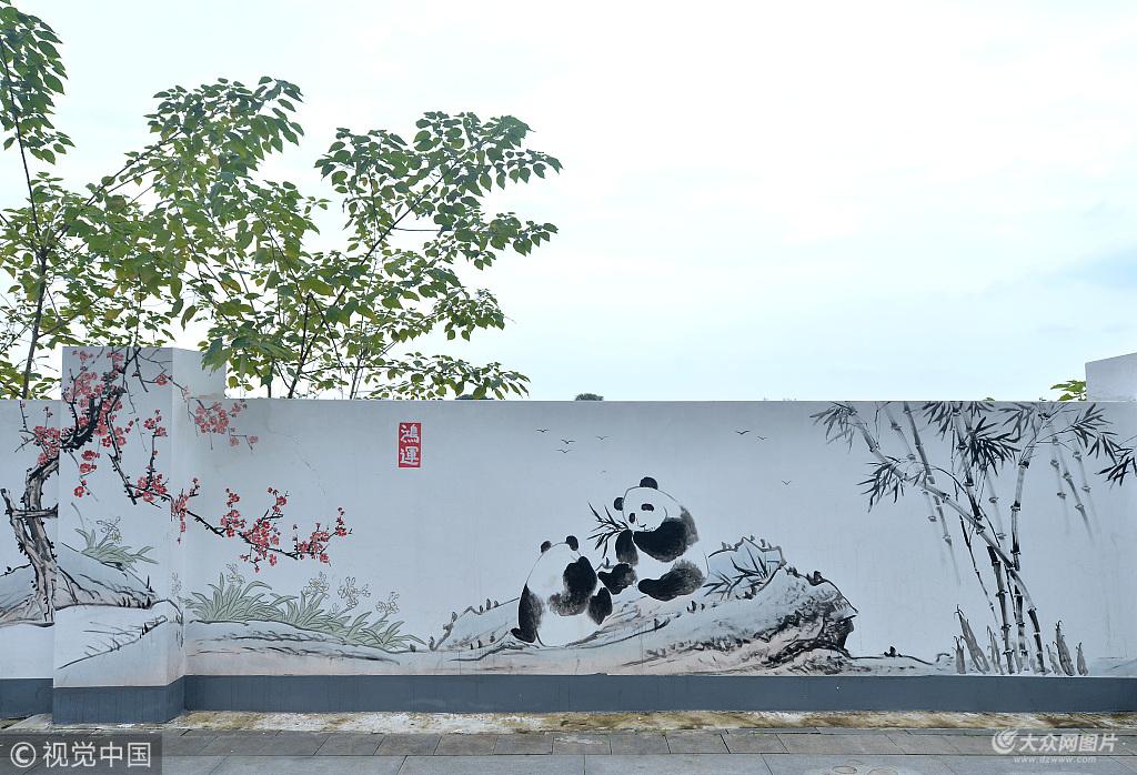 6月26日,有市民反应,称成都熊猫大道上惊现大批熊猫,延绵数千米,密密麻麻熊猫基地国宝跑出来了?肯定不是了,这是60位民间画师历时2个月,集体绘制的熊猫墙,绵延超过10里路。熊猫大道通向熊猫基地,熊猫大道充满熊猫文化,艺术家笔下的熊猫栩栩如生、千姿百态,啃竹子、扫地、睡觉、甚至手里还拿着四川特色美食串串的今后,来自各地的游客走到熊猫大道,一定会眼前一亮!(成都商报 陶轲/视觉中国) 据了解,这片熊猫墙全长5.