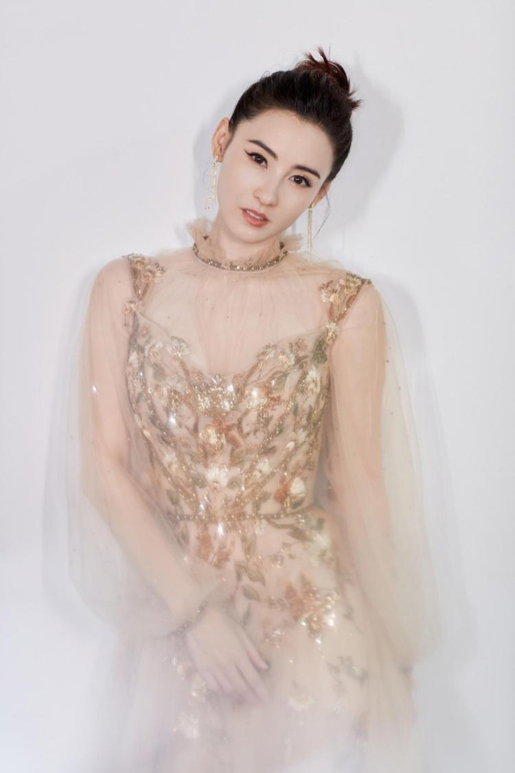 穿着张柏芝金色薄纱太阳花裙子 芳香的肩膀、眼睛、皮肤、阳气十足