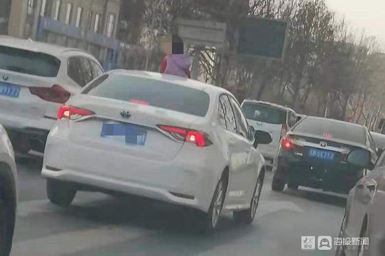 青岛:行车中孩子半个身子探出天窗 驾驶员妈妈挨处罚