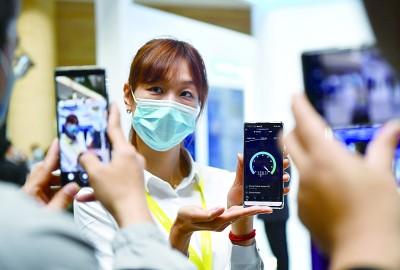 2021世界�信和信息社��日大��日前�_幕,工作人�T在大��上用手�C展示5G�W�j速度。新�A社�l